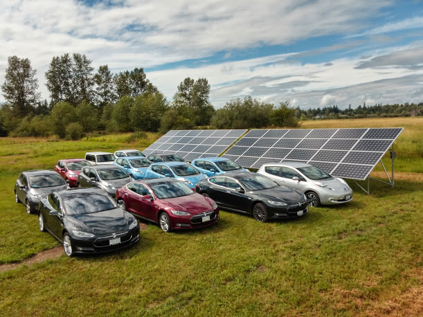 Thirteen 100% electric vehicles parked in front of our solar array. July 19, 2014. Photo by Steve Coram.